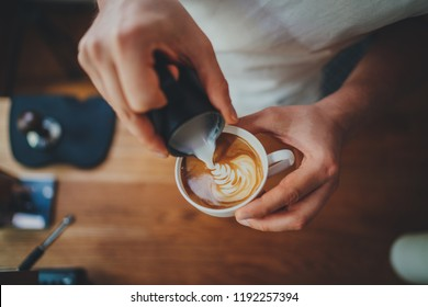 Top view shot of professional barista pouring milk from jar in to a cup of coffee, coffee being prepared by a barista. Focus on hands holding cup of coffee