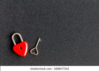 The top view shot of red heart padlock and key on black glitter background for valentines day with copy space