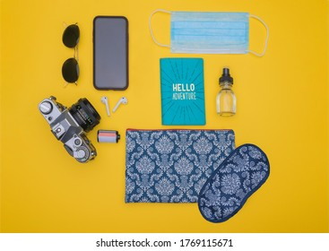 A top view shot of sunglasses, smartphone, ear pads, camera, film, passport holder, mask, sprayer, and pouch with a sleep mask on a yellow background