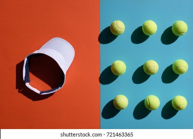 Top view shot of and tennis visor and balls placed on two toned surface