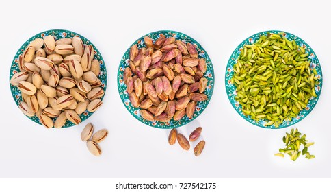 Top View Shot Of Three Different Shelled, Kernels and Sliced Pistachio Nuts In Turquoise Color Plates With Persian Designs Isolated On White Background, Low Calorie Healthy Delicious Dry Fruit Snack