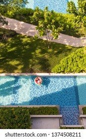 Top view shot of woman laying in flatable balloon in blue water swimming pool and green garden only one in sunlight.