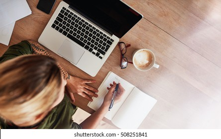 Top view shot of woman sitting at table with laptop and coffee writing on notebook. Female making to do list on diary.