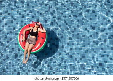 Top view shot woman wear sunglasses laying on balloon in blue water swimming pool with copy space, concept for luxury and happy lifestyle.