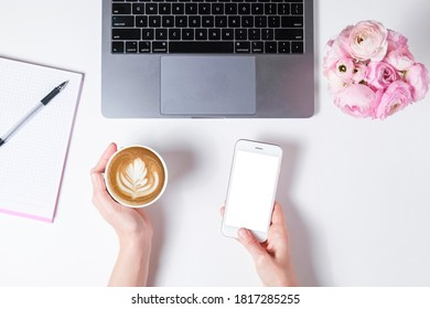 Top view shot of woman working on white laptop computer, textured table background. Feminine workspace with flowers bouquet. Close up, copy space.