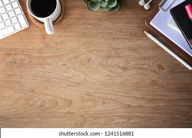 Top view shot of wooden office desktop with office supplies and copy space
