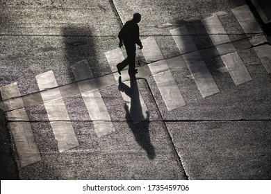 Top view of a silhouetted man and his shadow crossing the crosswalk