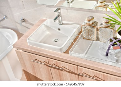 Top view of a silver taps and white sink on the wooden counter with soap and towel under the mirror near tub
