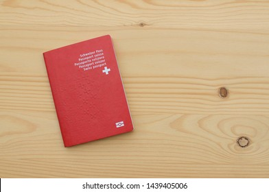 Top view of a single Swiss Passport on a wooden table