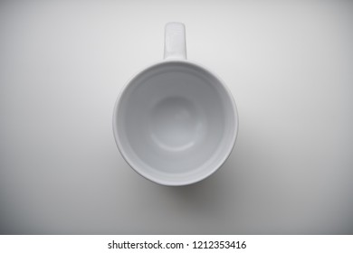 Top view of a Single White porcelain or ceramic mug isolated on a plain background