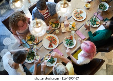 Top view of six casual friends sitting by wooden table served for dinner, enjoying meal and having chat