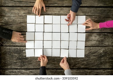 Top view of six hands, male and female, assembling a collage of blank white cards over textured wooden rustic boards.
