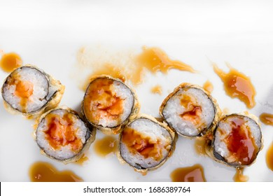 Top view of six pieces of mixed sushi rolls on a serving platter with soy sauce around them.