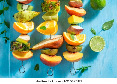 Top view of skewers with mix of fruits in summer