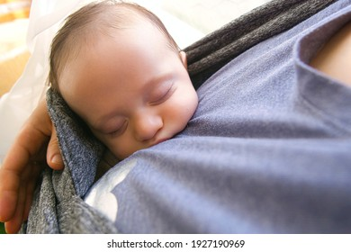 top view of sleeping baby being carried by his mother. three months