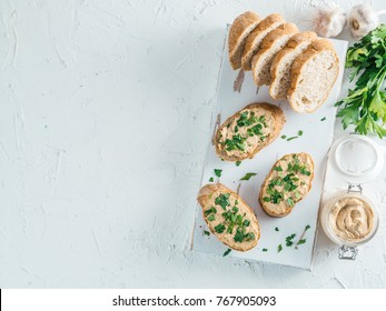 Top view of slice bread with homemade turkey pate and fresh green parsley on white rustic kutting board over white concrete background, Shallow DOF. Selective focus Copy space.