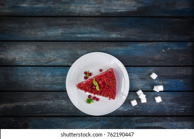 Top View. Slice of delicious Red velvet cake on a white plate with rafinated sugar on a colored wooden background