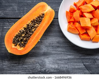 Top view of slice ripe papaya fruit in half and pieces in white plate on black wooden background.