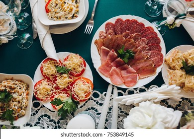 Top view of sliced cold meat, stuffed tomato snack and salads served on festive table. Sausage, ham, salami.