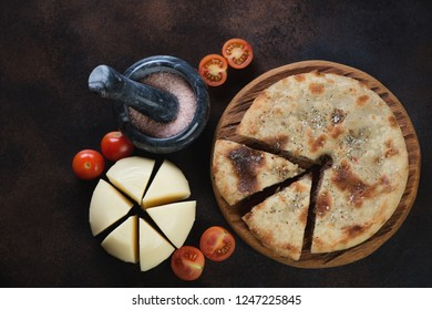 Top view of sliced ossetian pie, cherry tomatoes and suluguni on a dark brown metal background, horizontal shot