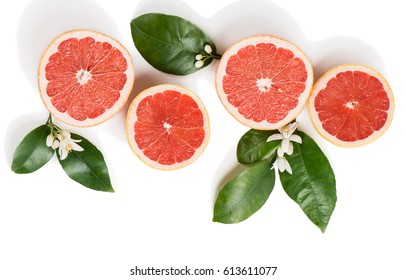 Top view of sliced red grapefruits with leaves and blossom isolated on white background.
