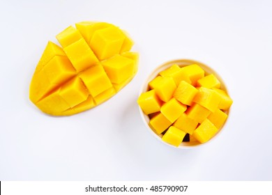 Top view of sliced ripe mango cubes on a white background.