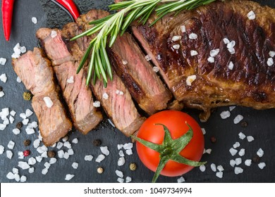 Top view of a sliced roasted prime Black Angus beef steak strip loin decorated with a rosemary, salt, peppercorns, tomato and chili peppers on black board.