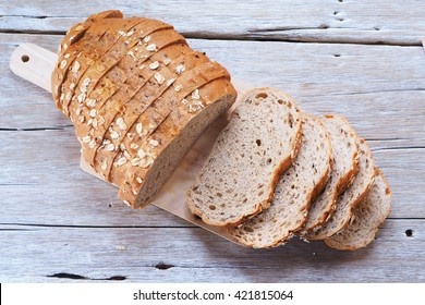 Top view of sliced wholegrain bread on a wooden cutting board.