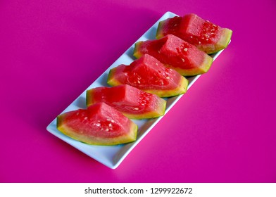 Top view of slices of watermelon in a white plate