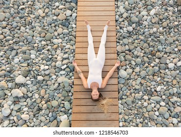 Top view - slim beautiful gorgeous blonde girl in a white suit resting lying on her back on a wooden platform among the stony beach in a warm summer evening. Concept of nirvana and relaxation