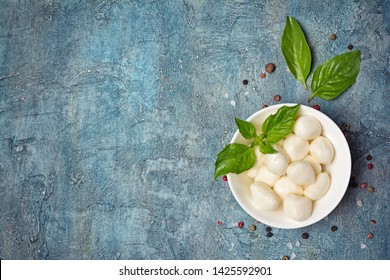 Top view of small balls mozzarella cheese with basil leaves as ingredients for light meals on blue concrete background with copy space