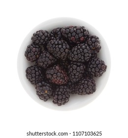 Top view of a small bowl filled with ripe blackberries isolated on a white background.