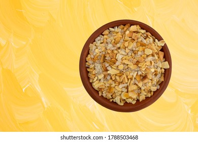 Top view of a small bowl filled with garlic and sea salt seasoning on a yellow wood painted background.