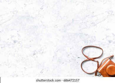 Top view of a small camera in a vintage brown leather case with shoulder strap isolated on a white marble table