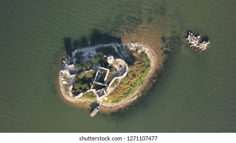 Top view of small island with ruins. Stock. Ruins of old house on small piece of land surrounded by sea. Forgotten place with moored boat surrounded on all sides by water