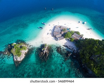 Top view of small isolated tropical island with white sandy beach and blue transparent water and coral reefs. Aerial shooting, speedboats, longtail boats, Khai Nok island, Phuket, Thailand.
