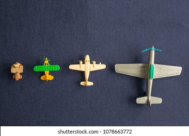 Top view of small miniature of toy planes. Colored plastic and wooden vintage midget aircrafts. Isolated on dark background