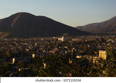 top view of a small town at the foot of the mountains in the rays of the evening sun