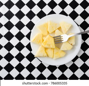 Top view of a small white plate with fresh pineapple slices with a fork on a black and white checkerboard tablecloth.