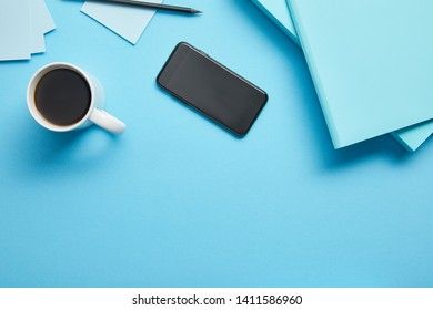 Top view of smartphone with blank screen and cup of coffeee at workplace on blue background