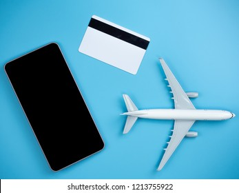 Top view of  smartphone , credit card and plane on blue isolated background with copy space.
