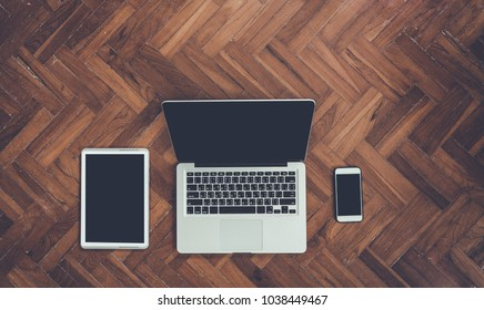 Top view smartphone and laptop with coffee cup, Airplane, Photos and Credit card on  wooden background.