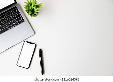 Top view Smartphone screen,pen,Laptop and Green plants on White desk Copy space