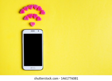 Top view of smartphone with the symbol of Wi fi from decorative hearts on yellow paper background. Internet technology and networking concept.