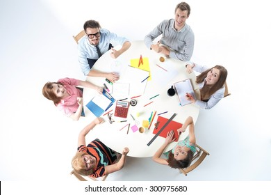 Top view of smilimg business team, sitting at a round table on white background.  concept of success