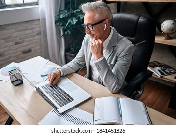 Top view of smiling adult businessman sitting in a chair at a desk and typing on a laptop in his office. Business concept