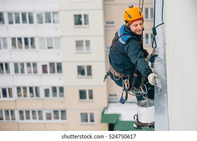 top view of smiling Industrial climber in helmet and workwear working at height. Risky work. Dangerous job