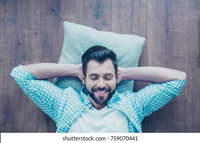 Top view of smiling man with bristle, lying on the floor with closed eyes, hands behind the head, he is dreaming about vacation, having rest from work