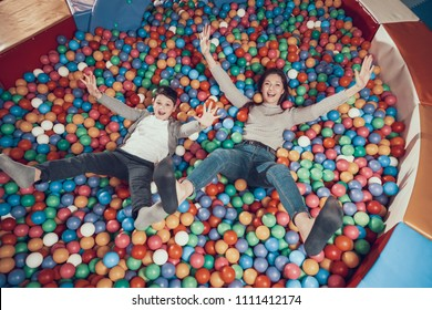 Top view. Smiling mom and son lying in pool with balls. Family rest, leisure. Spending holiday together with family. Entertainment center, mall, amusement park.