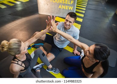 Top view of smiling two sport women and man training together in sport club. They are having great time together. Athletes are sitting on mats in triangle and connecting hands with joy
